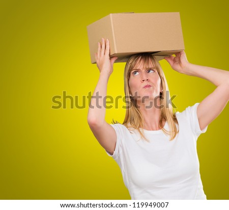 woman holding a box on her head against a yellow background - stock photo
