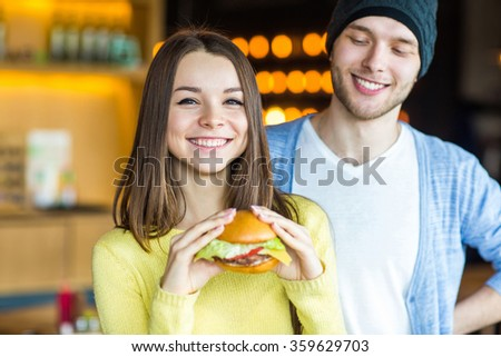 woman holding a burger. In the background, laughing man. Girl smiling with burger in hand - stock photo