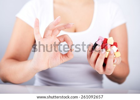 Woman holding a candies in his hand and the other hand is doing ok gesture - stock photo
