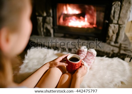 Woman holding a cup of tea by the Christmas fireplace. Woman relaxes by warm fire with cup of hot drink and warming up her feet in woollen socks. Close up on feet. Winter, Christmas holidays concept. - stock photo