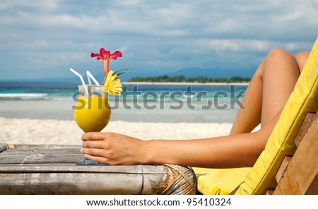 Woman holding a fruit cocktail on a tropical beach - stock photo