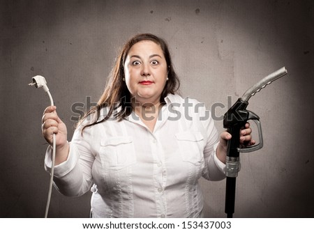 woman holding a fuel pump nozzle and an electric cable - stock photo