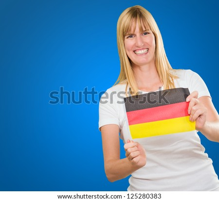 woman holding a german flag against a blue background - stock photo