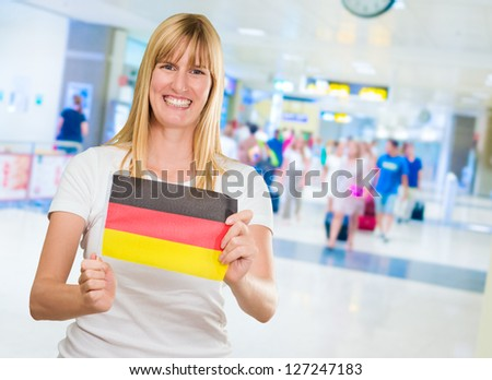 woman holding a german flag in an airport - stock photo