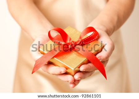 Woman holding a gift box in a gesture of giving. - stock photo