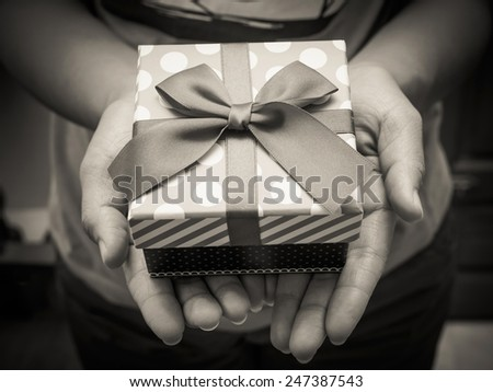 Woman holding a gift box in a gesture of giving with black and white effect - stock photo