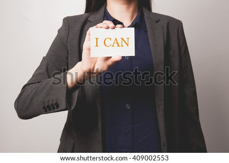 Woman holding a I Can word on a paper sheet - stock photo