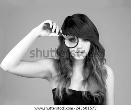 Woman holding a magnifying glass in black and white - stock photo