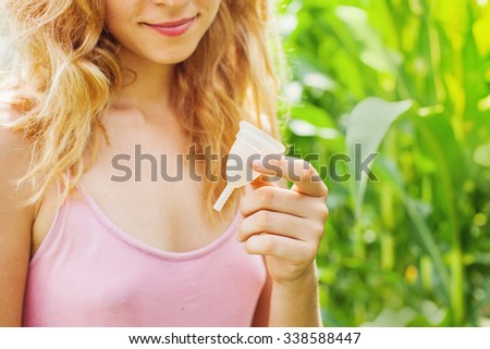 woman holding a menstrual cup standing against green natural background (soft focus on cup) - stock photo