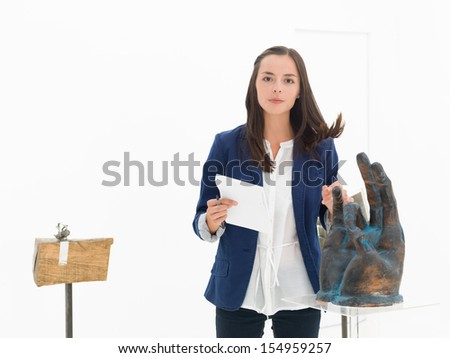 woman holding a notebook surprised in a museum while arranging her hair - stock photo