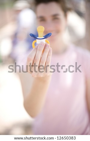 woman holding a pacifier up to the camera with her hand while wearing a pink shirt and smiling outside - stock photo
