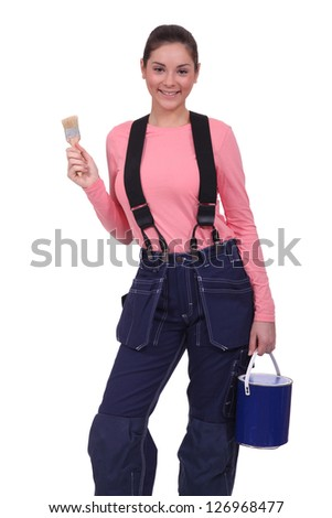 Woman holding a paintbrush and can of paint - stock photo
