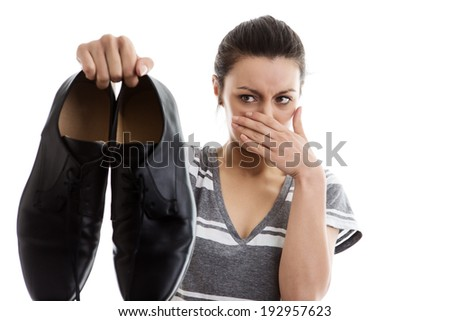 woman holding a pair of men smelly work shoes in the air not looking to happy - stock photo