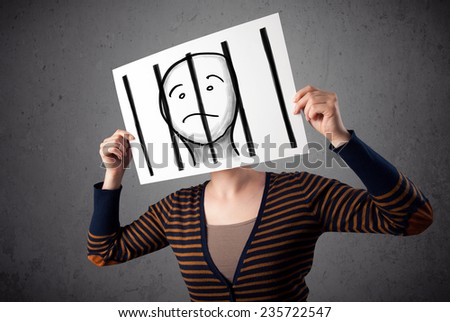 Woman holding a paper with a prisoner in jail behind the bars on it in front of her head - stock photo