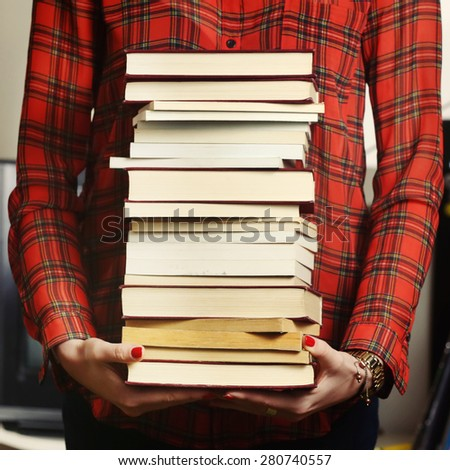 Woman holding a pile of books for studying concept. - stock photo