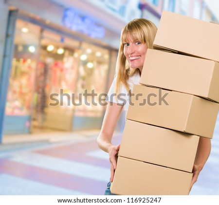 woman holding a pile of boxes at the street - stock photo