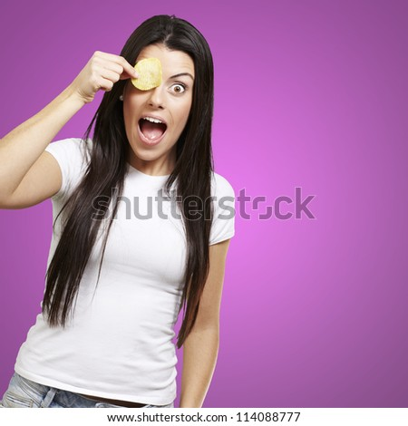 woman holding a potato chip in front of her eye against a pink background - stock photo
