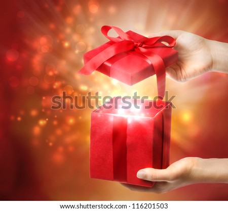 Woman holding a red gift box on a bright holiday lights background - stock photo