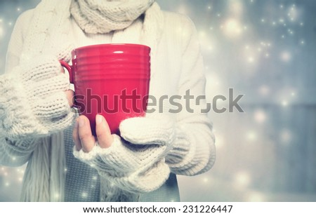 Woman holding a red mug in snowy night - stock photo