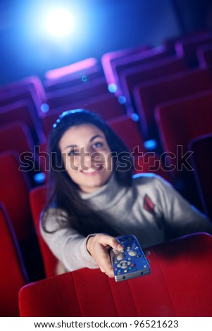 woman  holding a remote control TV, at a  movie theater. conceptual image - stock photo