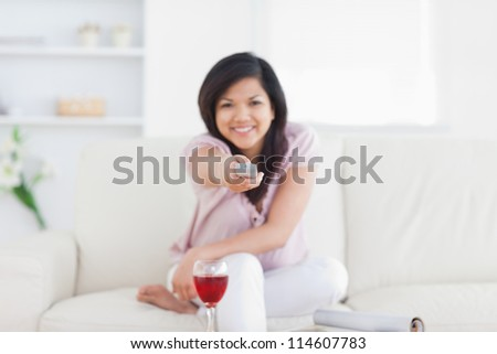 Woman holding a remote while sitting in a living room - stock photo
