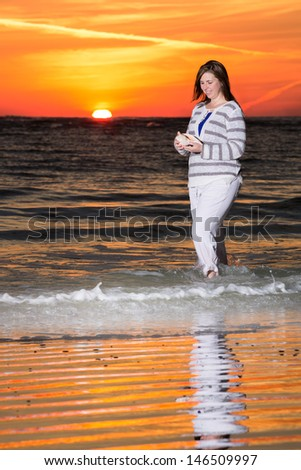 Woman Holding a Shell on the Beach During Beautiful Sunset - stock photo