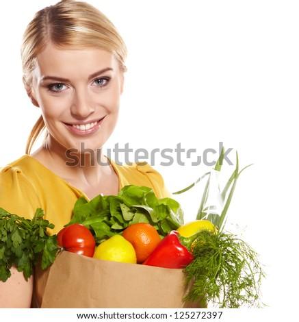 woman holding a shopping bag full of groceries, mango, salad,  radish, lemon, carrots on white background - stock photo