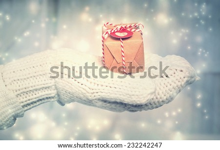 Woman holding a small gift box with heart tag in snowy night - stock photo