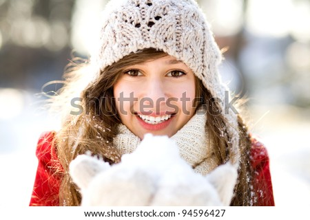 Woman holding a snowball - stock photo