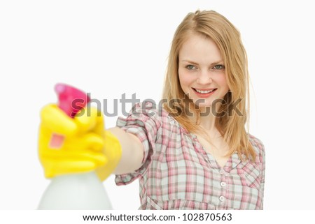 Woman holding a spray bottle while smiling against white background - stock photo