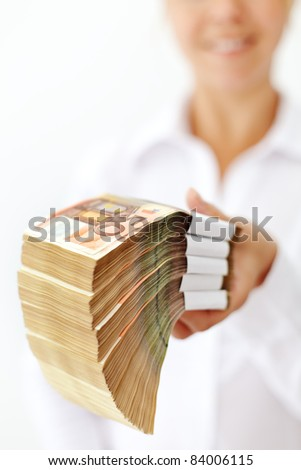 Woman holding a stack of euro banknotes - extreme shallow depth - stock photo
