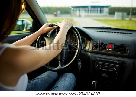 Woman holding a steering wheelr. Focus on hands - stock photo