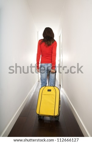woman holding a suitcase in white passage indoor - stock photo