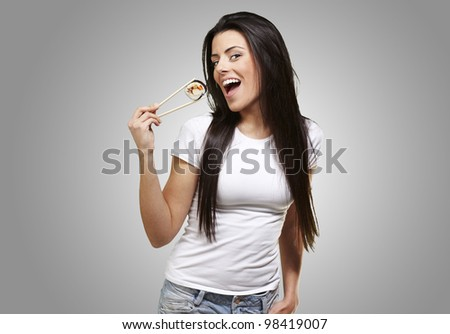woman holding a sushi piece with chopsticks against a grey background - stock photo