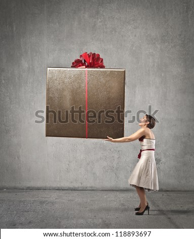 Woman holding a very big present - stock photo