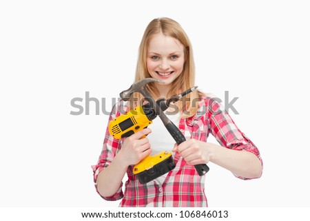 Woman holding an electric screwdriver and a hammer against white background - stock photo