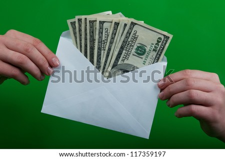 woman holding an envelope full of money - stock photo