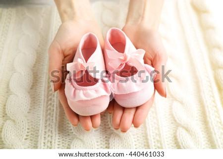 Woman holding baby booties, closeup - stock photo