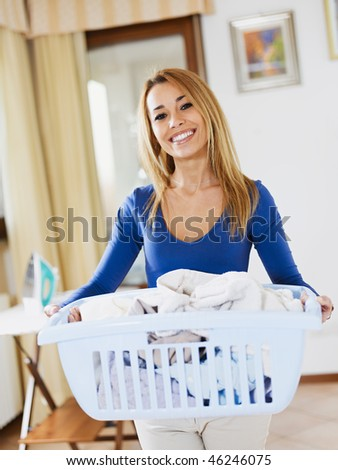 woman holding basket of laundry and looking at camera - stock photo