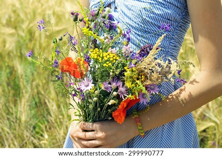 Woman holding beautiful bouquet of wildflowers outdoors - stock photo