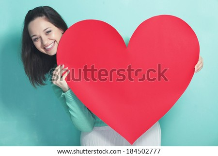 Woman holding big red heart on blue aqua background - stock photo