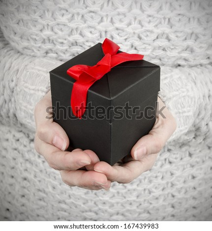 woman holding black gift box with red ribbon - stock photo