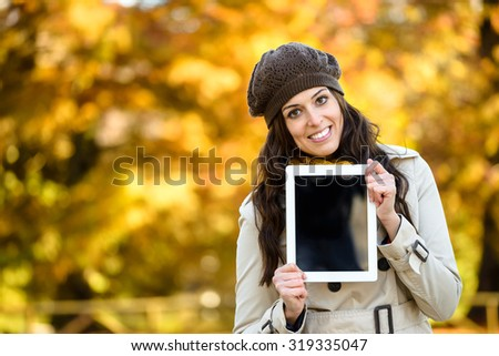 Woman holding blank screen digital tablet in autumn outdoor. Young female holding touchpad for copy space message or information. - stock photo