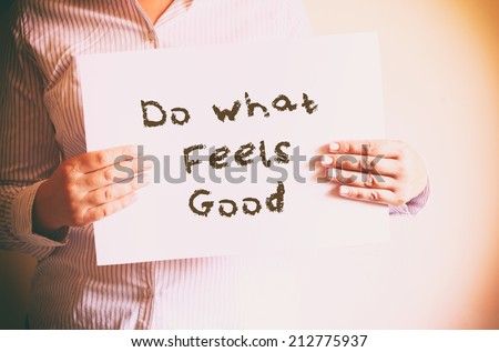 "woman holding board with the phrase ""do what feels good"" written on it. retro filtered image. - stock photo"