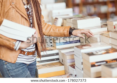 Woman holding books at a bookshop. - stock photo