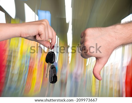 Woman holding car key, man showing thumb down at auto center - stock photo