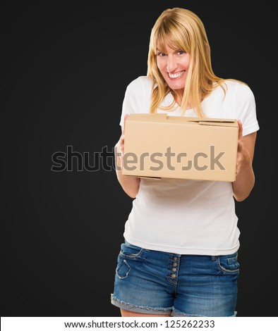 Woman Holding Cardboard box against a black background - stock photo