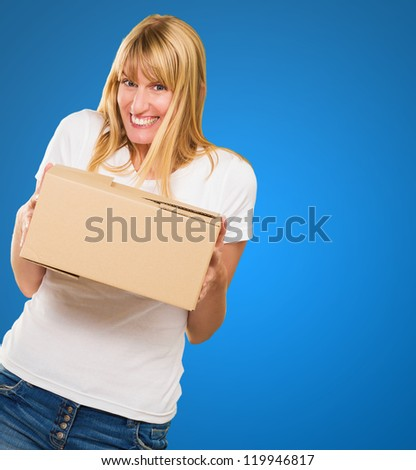 Woman Holding Cardboard box against a blue background - stock photo