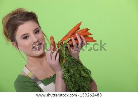 Woman holding carrots - stock photo