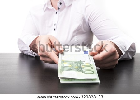 Woman holding cash in euro on desk isolated on white background - stock photo